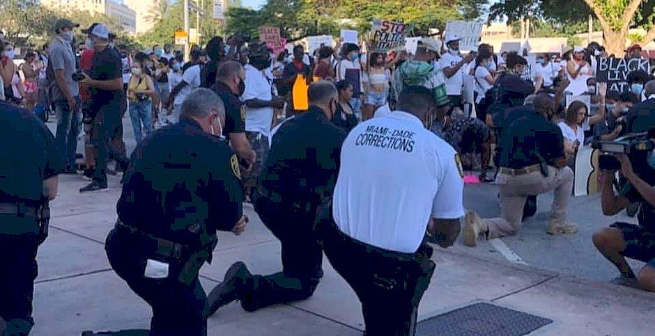 Un momento de policías y manifestantes orando juntos,Oración de policías y manifestantes en Miami