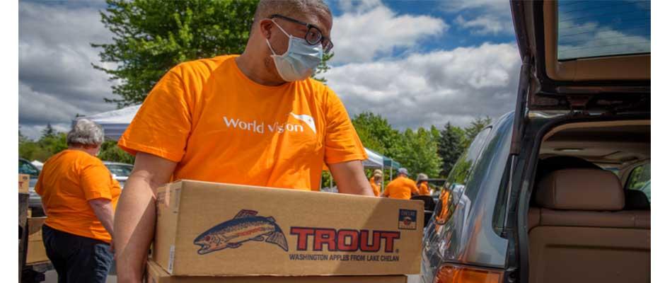 Un voluntario de Visión Mundial cargando una caja de comida / Foto: Andrea Davis, Visión Mundial,
