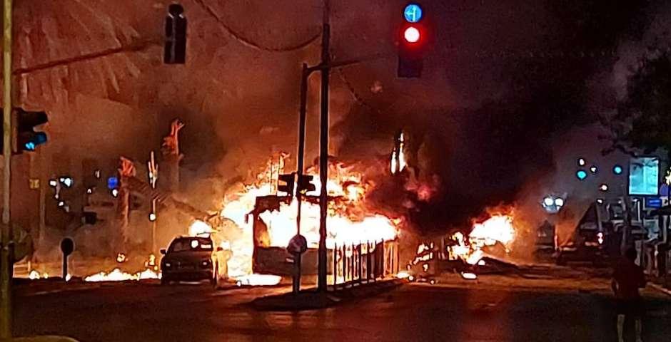 Vehículos ardiendo en una calle de Tel Aviv tras el impacto de un cohete. / Twitter @IDF,
